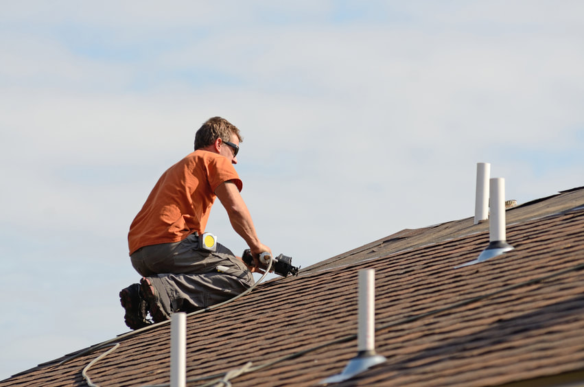 Photograph of roofer using nail gun to attach shingle to a new roof