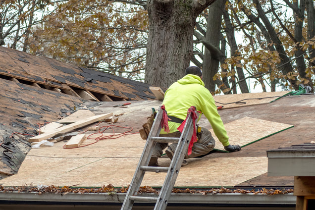 Picture of a man doing roof tear off of an old roof